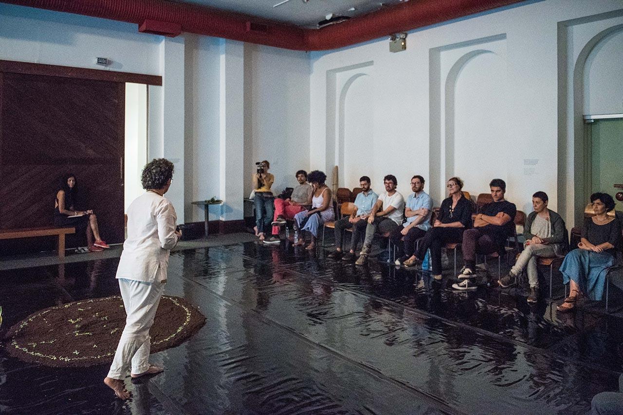Pessoas numa sala sentadas em cadeiras observando a artista em sua performance. Ela está vestida de branco.