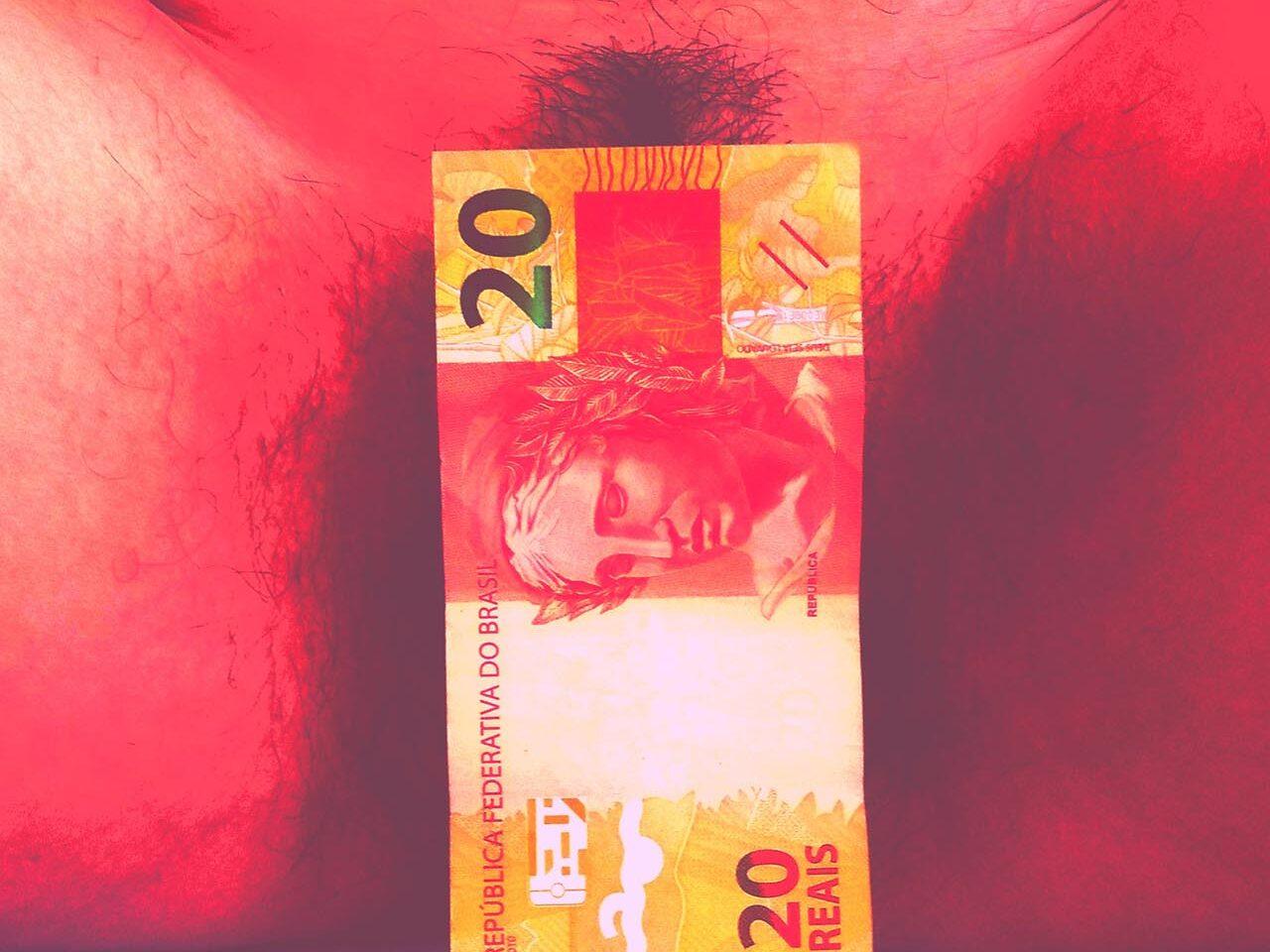 Flávia Naves – O capital é capilar - Nota de vinte reais de fronte a uma vagina. Foto com tom avermelhado