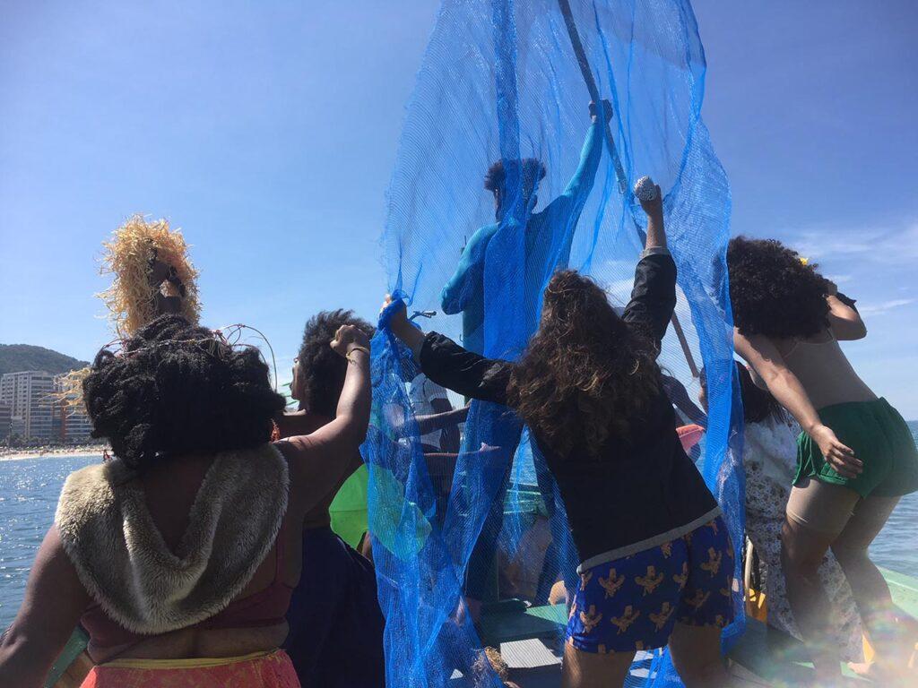Monumoments – Muitas mulheres comemorando dentro de um barco ao mar.